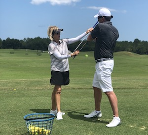 Photo - LPGA golf instructor giving a golf lesson to man