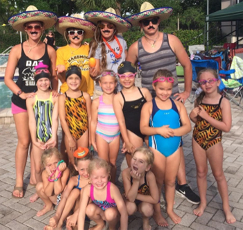 Photo adults with sombreros with children with goggles standing for group photo poolside