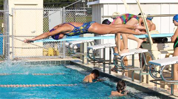 Photo woman diving off diving board into pool