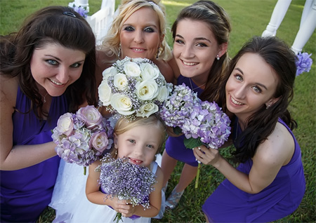 Photo closeup of Bride, bridesmaids and flower girl holding bouquets