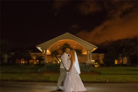 Photo bride and groom in front of clubhouse kissing at night