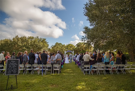 Photo of Outdoor Wedding Ceremony at Bardmoor showing guest standing for bride walking with father in ceremony set up