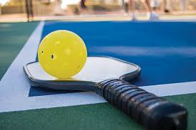 Photo closeup of Pickleball paddle and ball