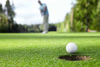Photo close up of golfer making putt in hole