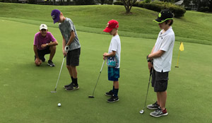 Photo Dana Saad PGA Golf Instructor teaching a lesson to 3 junior golfers
