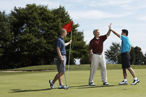 Photo Generic three male golfer's celebrating on the green