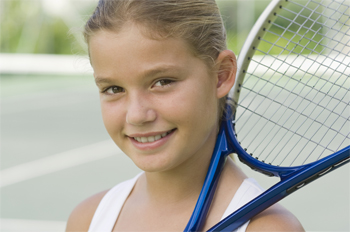 Photo - Close up young girl holding tennis racquet