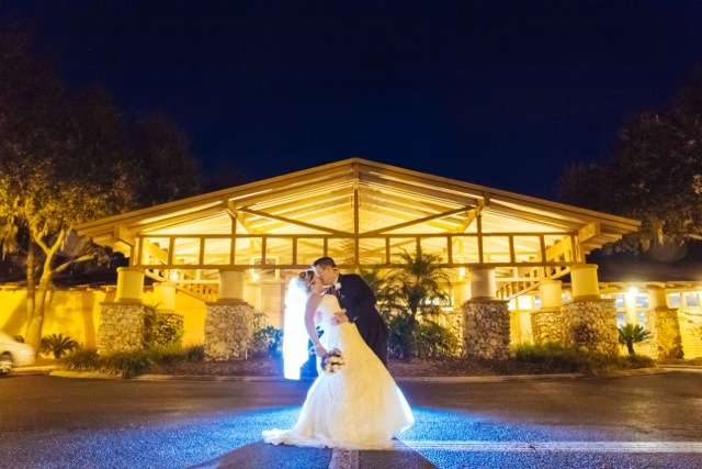 Photo - bride & Groom kissing at night in front of Clubhouse
