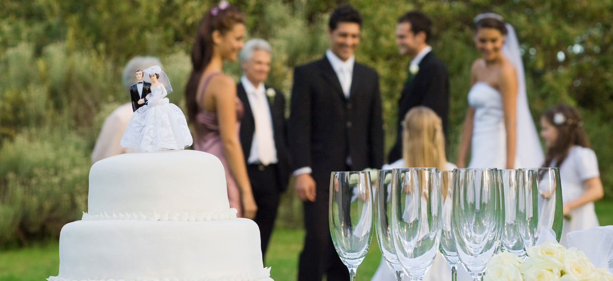 Photo Header River Hills Country Club Wedding Cake close up with Bridal party in backround