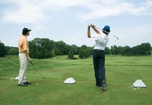 Photo - 2 golfers on Driving range on hitting ball 1 watching