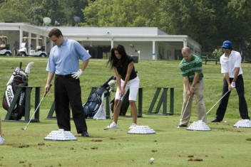 Photo four golfers on driving range